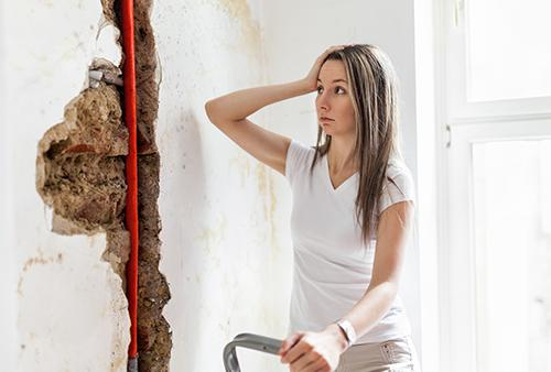 Woman looking at water damage in her home.
