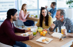 Men and women eating lunch at a table.
