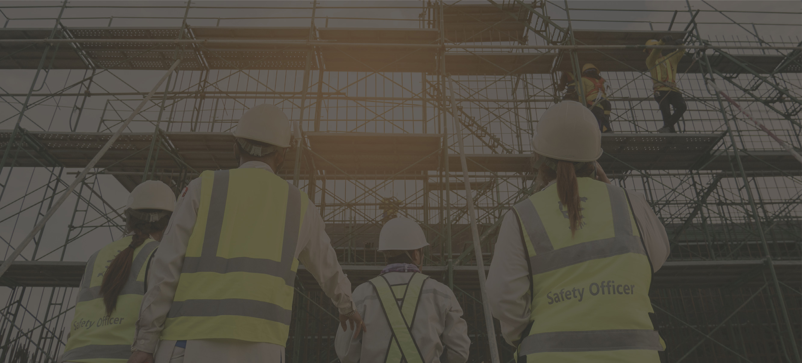 Darkened image of a group of people at a construction site with safety vests