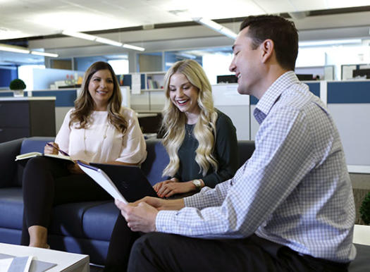 Angelica Alaniz, Morgan Agster and Cliff May sit at couches in the Phoenix office