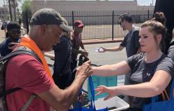 MJ Associate hands a homeless man supplies