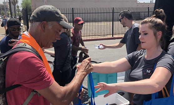 MJ Associate hands a homeless man supplies